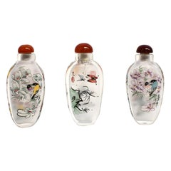 Three Églomisé Reverse Painted Snuff Bottles with Magnolia and Orchid