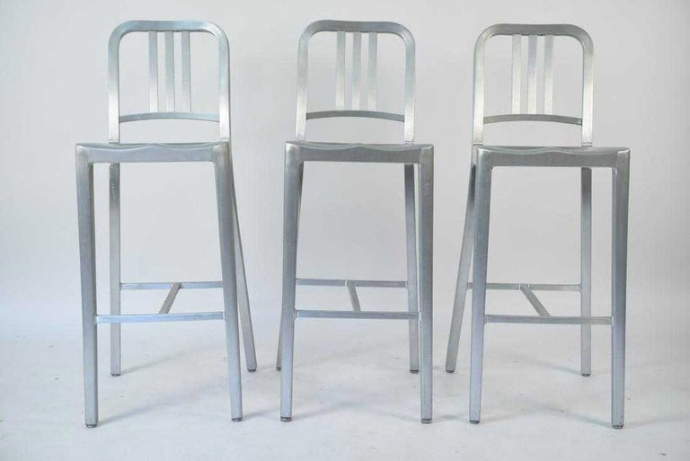 From the movie set of 'The Upside', these classic Emeco aluminum Navy bar stools designed by Philippe Starck was first built for use on US submarines in 1944. Stools have original round metal glide with a Lexan cap, for the Navy collection. For