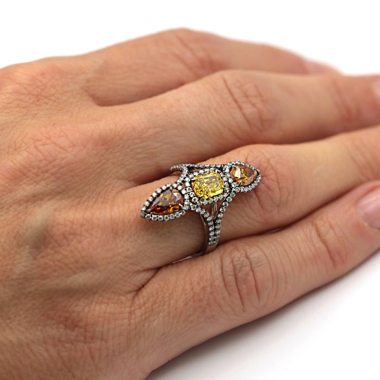 Eighteen karat vertical three diamond ring. The ring is made up 3 diamonds with certificates from the Gemological Institute of America. The center diamond is a radiant cut diamond weighing 1.03 carats and is Fancy Vivid Yellow. The center diamond is