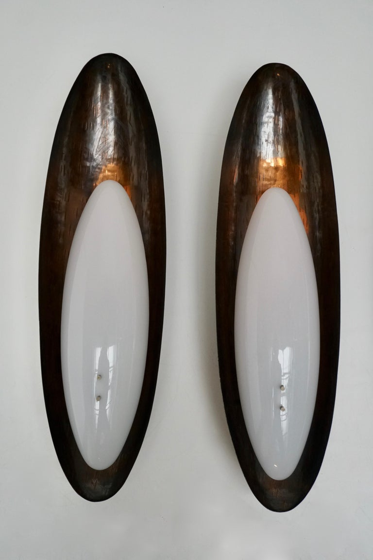 Three sconces by Reggiani. Designed and manufactured in Italy, circa 1960s. Hand-hammered copper and Perspex. Takes two E27 25w maximum bulbs.