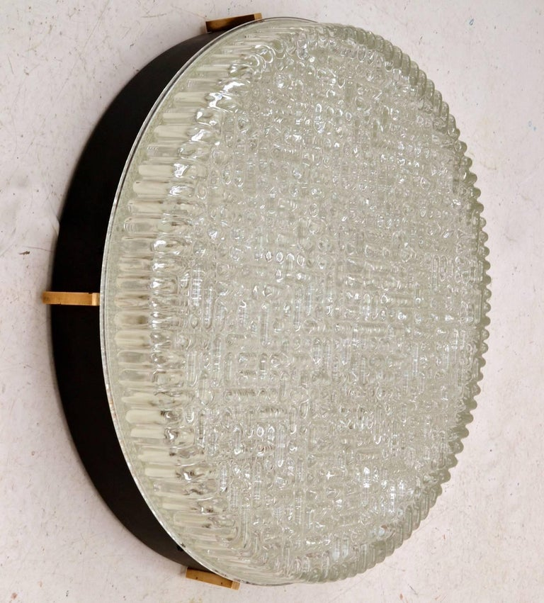 Three large flushmount pendants or wall lights in pressed glass with a typical 1960s abstract geometric motive hold by a black metal frame with brass details, by N Leuchten. They have never been used of which some are still in their original