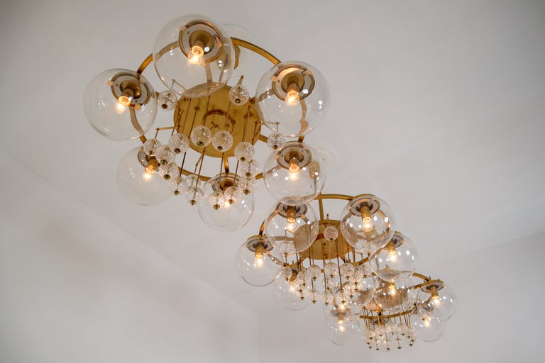 Large hotel chandeliers with brass fixture and large hand blowed glass. The chandeliers with brass frame consist of six lights, formed in a circle, with glass shades. The pleasant light it spreads is very atmospheric. Completed with the structured