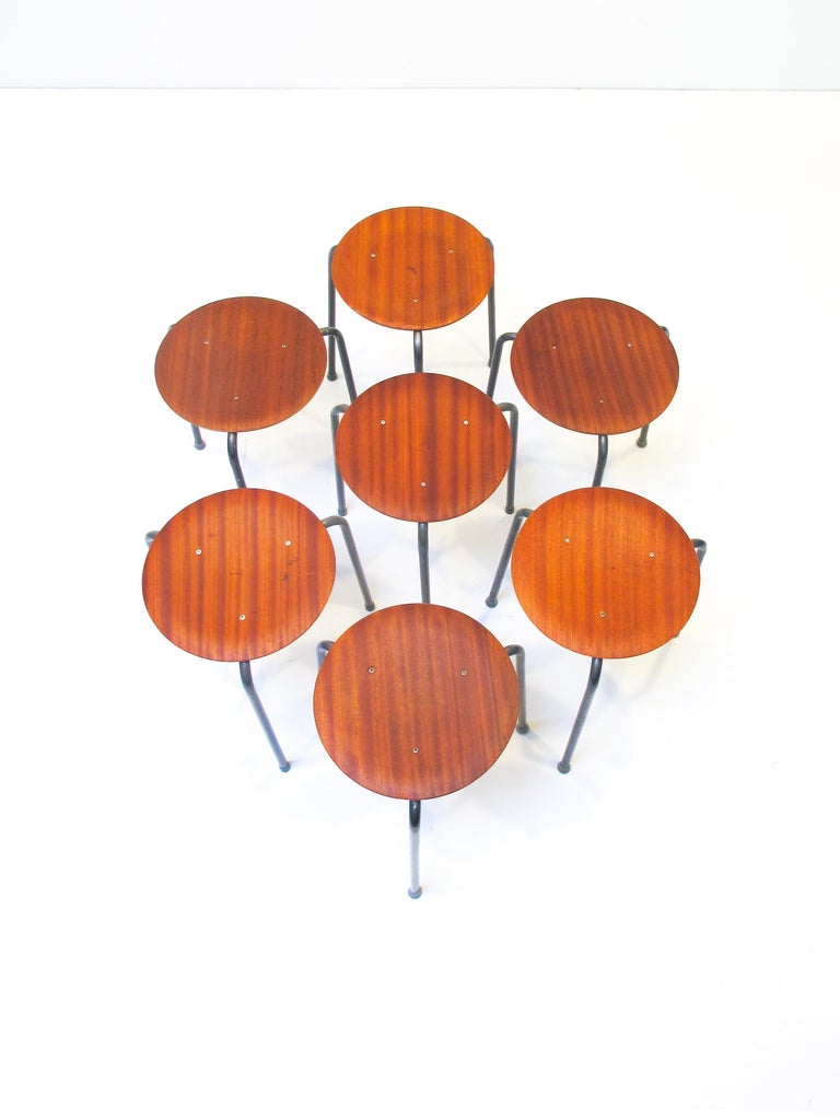 Three legged stools very much alike the stool that Arne Jacobsen designed for Fritz Hansen at the same time period.  This model was mass built and has lower quality with visible skrevs in the siting and molded plywood seating.