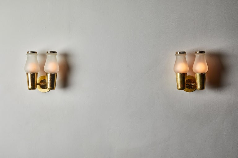 Three pairs of sconces by Gino Sarfatti. Manufactured in Italy, circa 1950s. Glass diffusers with brass hardware. Rewired for US junction boxes. Each light takes one E27 100w maximum bulb.