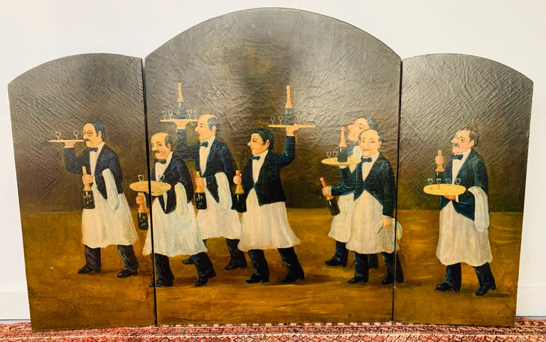 This lovely three panel folding fireplace screen is hand painted on wood. The screen features a scene of a group of men waiters in a high-end Steak House or restaurant serving bottles of champagne.   This screen will definitely set the mood in