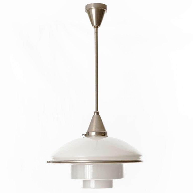 One of three rare pendant lights model 'Megaphos' by Otto Müller for Sistrah, manufactured in Germany in Bauhaus in 1930s. The lamp shade consists of two parts which are held together with a nickeled brass ring. The upper part is made of opaline