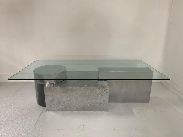 Three-piece geometrical coffee table. Unique base comprising of three sections which depicts 3-D puzzle pieces. Surfaces are textured and flat. Has the original glass. Each piece has a painted silver finish. Paul Evans style.