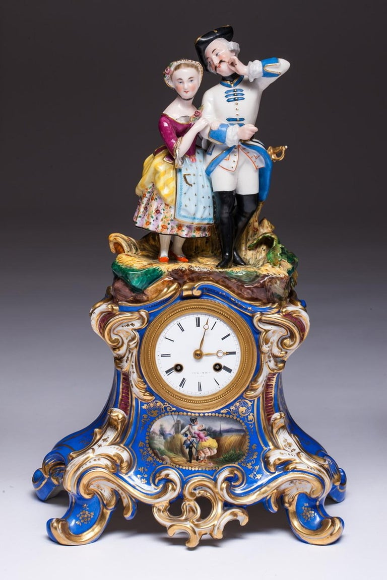 Three-piece old Paris porcelain mantel garniture in the rococo manner. A two-piece old Paris porcelain clock. The top half features a figures of a couple, soldier and a woman standing on the grass. The bottom half of the clock is painted with a