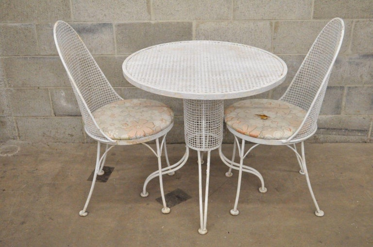 Very rare vintage three-piece iron metal mesh patio bistro dining set believed to be Russell Woodard. Item features iron metal mesh construction, round pedestal base dining table, two dining side chairs, round seats, oval backs, great modernist