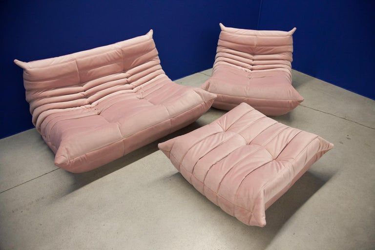 This Togo living room set was designed by Michel Ducaroy in 1974 and was manufactured by Ligne Roset in France. It has been reupholstered in pink high quality velvet, and is made up of the following pieces, each with the original Ligne Roset logo