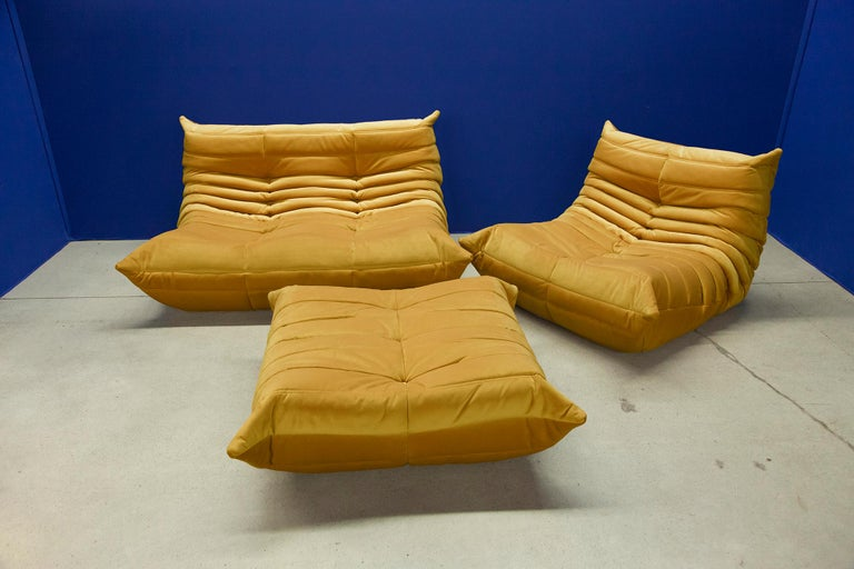 This Togo living room set was designed by Michel Ducaroy in 1974 and was manufactured by Ligne Roset in France. It has been reupholstered in golden yellow high quality velvet, and is made up of the following pieces, each with the original Ligne