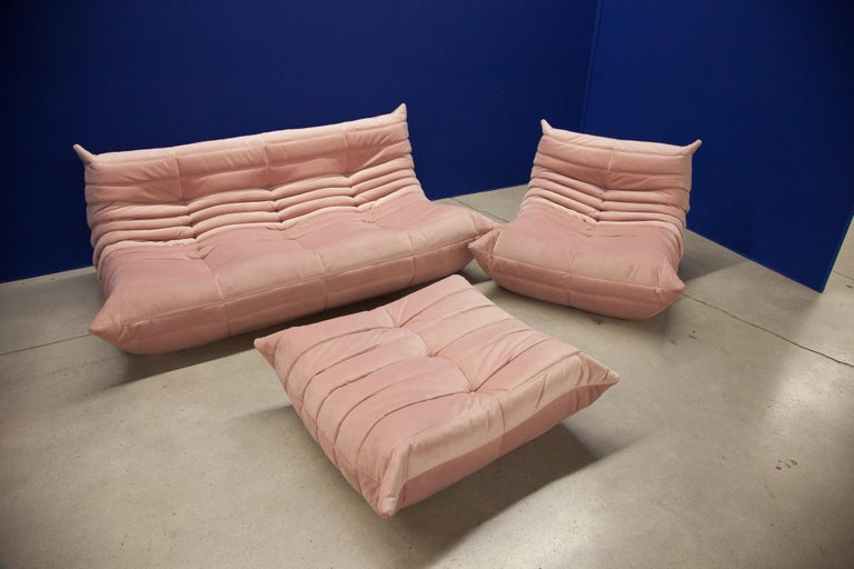 This Togo living room set was designed by Michel Ducaroy in 1973 and was manufactured by Ligne Roset in France. It has been reupholstered in pink high quality velvet, and is made up of the following pieces, each with the original Ligne Roset logo