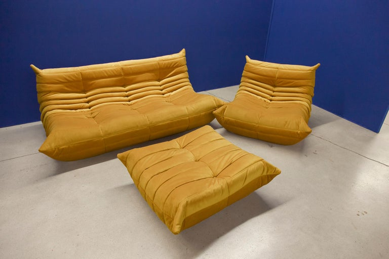 Three-piece Togo set, Design by Michel Ducaroy, manufactured by Ligne Roset this Togo living room set was designed by Michel Ducaroy in 1974 and was manufactured by Ligne Roset in France. It has been reupholstered in golden yellow high quality