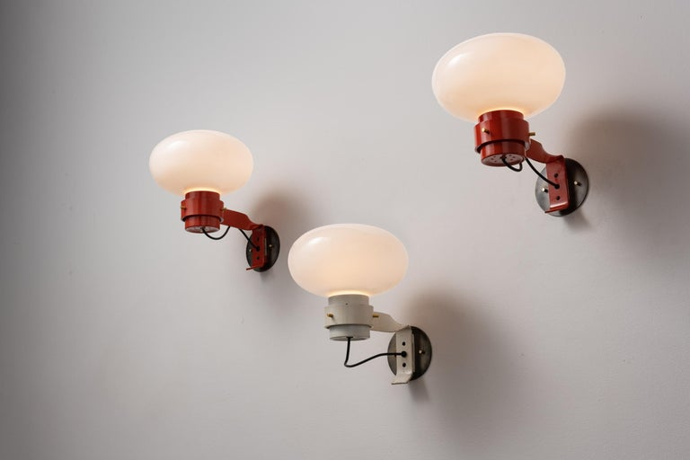 Three sconces by Martinelli. Manufactured in Italy, circa 1960's. Brushed satin glass diffuser, painted metal armature. Custom brass backplates. Rewired for U.S. standards. We recommend one E27 60w maximum bulb per fixture. Bulbs not included.