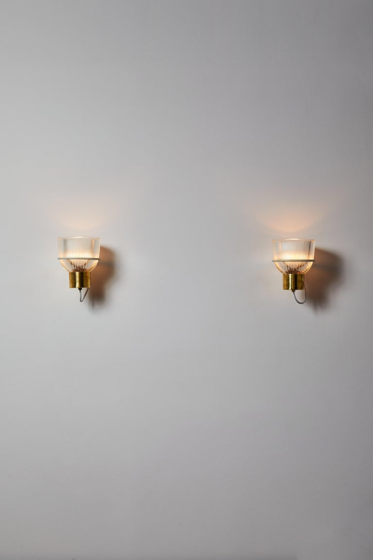 One sconce by Sergio Asti for Candle. Designed and manufactured in Italy, circa 1950s. Glass, brass, custom brass backplates. Rewired for U.S. standards. We recommend one E27 100w maximum bulb. Bulbs provided as a one time courtesy. Priced and sold