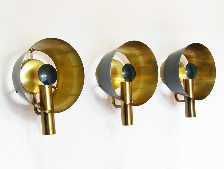 A set of three sculptural 1960s brass wall lights by Danish makers Lyfa.  Evoking 20th century aeronautics, the lights are made of brass with racing green lacquer. The brass reflectors emit spectacular golden light.  They are in excellent