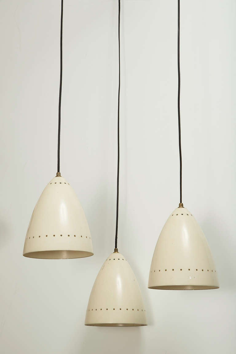 Three Shade Chandelier designed in Italy circa 1950s. Painted metal shades with perforation. Brass hardware and custom canopy. Wired for US junction boxes. Each shade takes one E27 60w maximum bulb