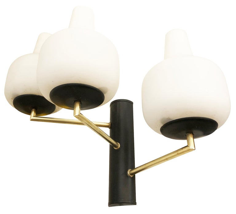Pair of Stilnovo wall lights, each with three staggered frosted glass shades on a brass and black lacquered frame. Three candelabra bulbs per sconce.  Condition: Excellent vintage condition, minor wear consistent with age and use.  Measures:
