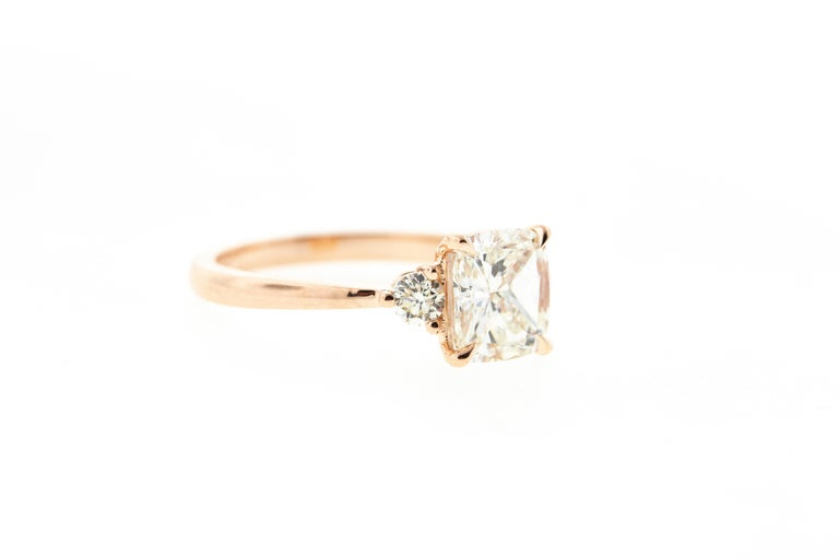 This Three Stone Cushion Cut diamond engagement ring is crafted in 14KT rose gold, and contains a Cushion shape Diamond (1.51 total carat weight, J color, VS2 clarity). With two side stones, a tapered shank and a raised profile, this ring is an