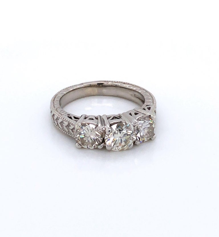 Admire the extra detail of the fancy fourteen karat 14k white gold antique style setting that adds to the classic beauty of this fine three stone diamond engagement ring.  Prominently displayed are three round brilliant cut diamonds with the center