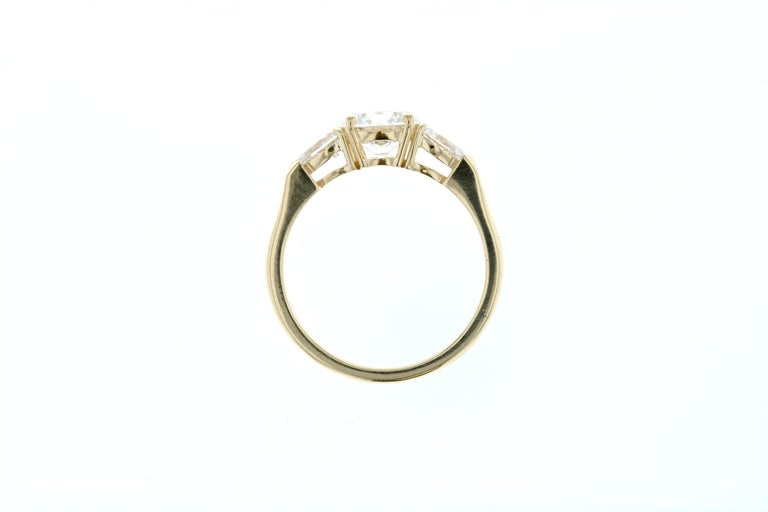 This stunning engagement ring is crafted in 18KT yellow gold, and contains a Round Diamond (1.13 total carat weight, H color, SI1 clarity) surrounded by 2 pear shape diamonds (0.39 total carat weight, H color, SI clarity). A perfect way to