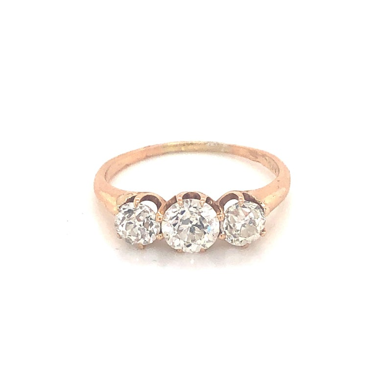 A three stone diamond ring, set with old European cut diamonds in a claw setting, mounted in 18ct yellow gold. The centre diamond weighs approximately 0.70ct. Estimated total diamond weight 1.30 carats. Makers mark AF & Co.  Finger size O UK / 7 US.