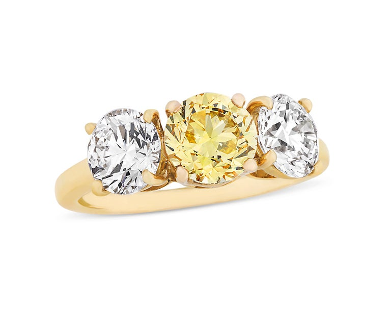 This classic three-stone ring from the celebrated house of Cartier is set with three extraordinary stones. At its center rests a round brilliant-cut fancy vivid yellow diamond weighing 1.24 carats. Certified by the Gemological Institute of America