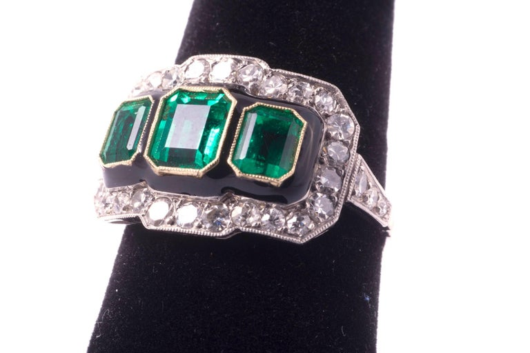 Gorgeous emerald and diamond ring. The center emerald weighs approximately 1.00cts, and the two emeralds on the side weigh approximately .50cts each. All the emeralds are rectangular step cut. The emeralds have excellent, rich, medium green color