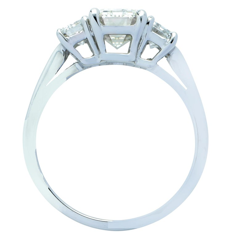 Exquisite engagement ring crafted in platinum, showcasing a gorgeous emerald cut diamond weighing 1.79 carats, K color, VS1 clarity, adorned with two emerald cut diamonds weighing .82 carats total, J color, VS2 clarity. The seamless face of this