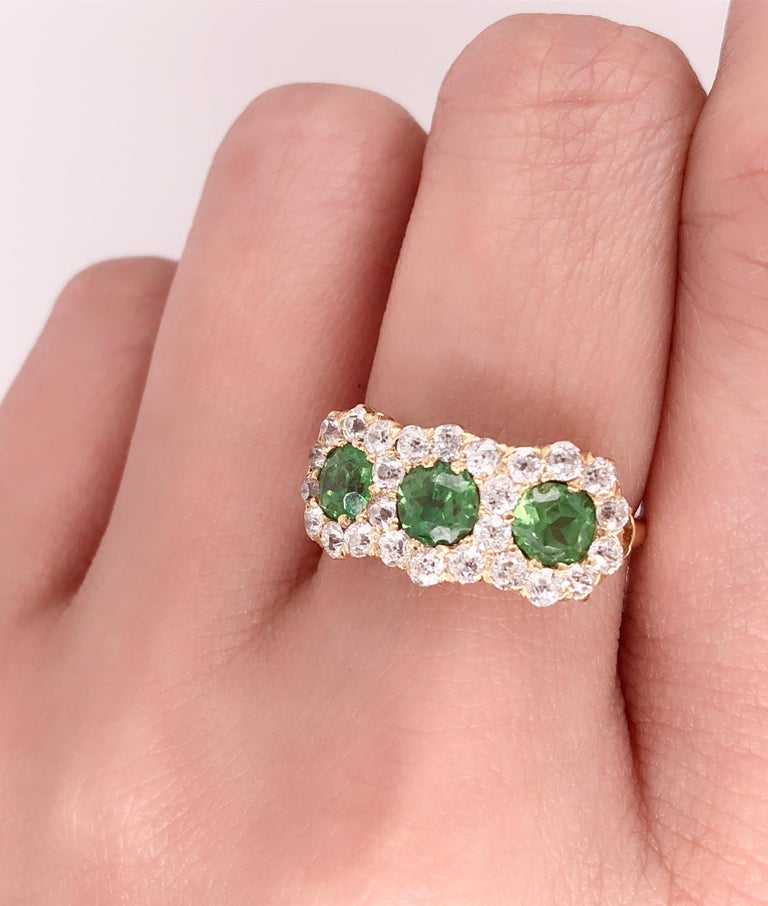Three Stone Emerald & Diamond Modern Ring. . Housing approx. Three sixty point round emerald stones for a total of 1.8 ct. each flanked by a total group of 25 round diamonds approx .05 diamonds for a total 1.25 ct of diamonds. Ring Size