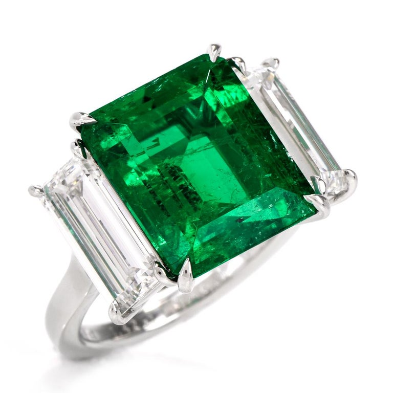 This stunning three stone emerald and diamond ring is crafted in solid platinum. Showcasing a prominent high quality genuine rectangular emerald-cut Colombian emerald approx. 6.70 carats with no treatments, except minor oil and measuring 13.00 x