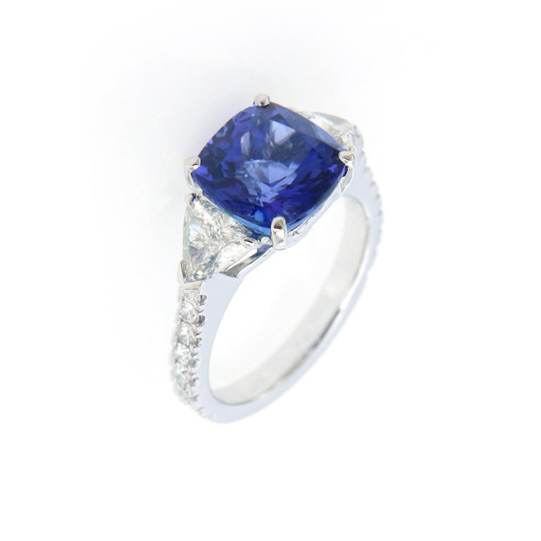 This stunning three stone ring has a 3.62ct tanzanite center stone, surrounded by half carat trillion cut diamonds in G SI qualiy. The band is set with G colored diamonds in 18k white gold. Truly a beautiful gemstone and ring.   The ring is in a