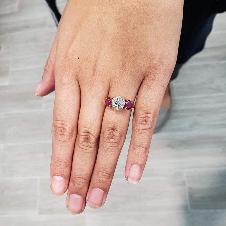 A sparkling 1.78 carat round diamond takes center stage in this ruby diamond engagement ring. Accenting the center stone are 2 color-rich rubies set in 4 prongs made with 14k yellow gold. Rounded composition for a seamless and comfortable fit. Size