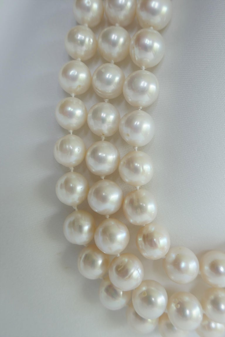 This three strand white cultured pearl necklace sits beautifully on the neck. The pearls are 10-11mm,  have great luster and little blemished. The necklace is individually knotted on silk thread. Although, a classical design the size make it more