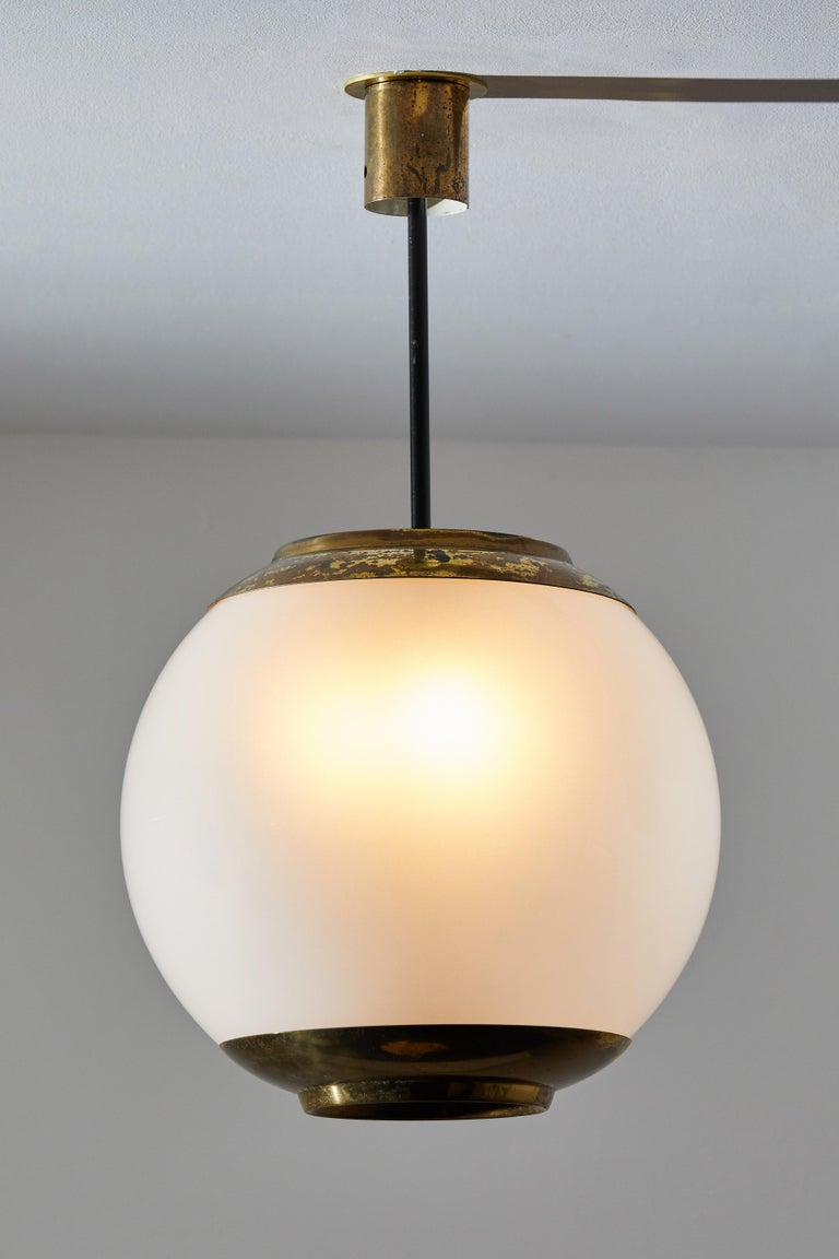 Three suspension lights by Caccia Dominioni for Azucena. Designed and manufactured in Italy, circa 1950s. Opaline glass, brass. Rewired for U.S. junction boxes. Original canopy, custom brass ceiling plate. Each light takes one E27 100w maximum bulb.