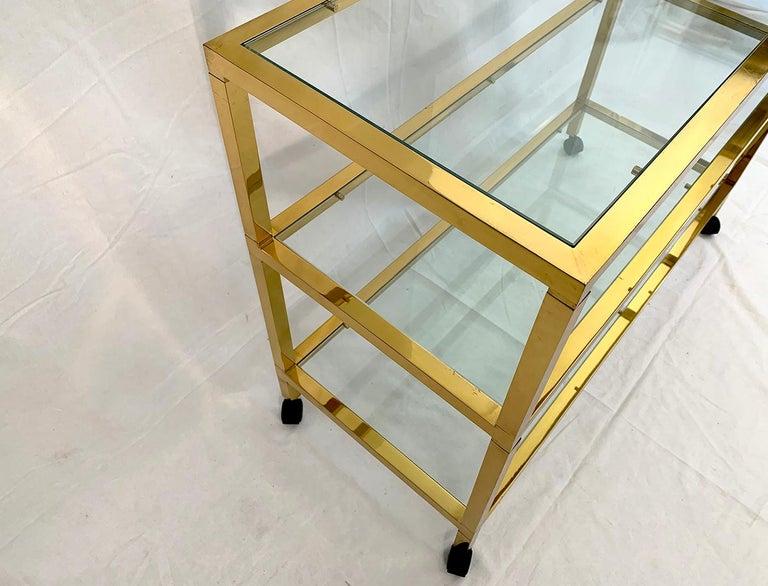 Beautiful brass three-tiered console or bar with transparent glass top, on wheels, 1970s.  Superbe console/bar à trois niveaux en laiton avec plateau en verre transparent, sur roulette, 1970s.
