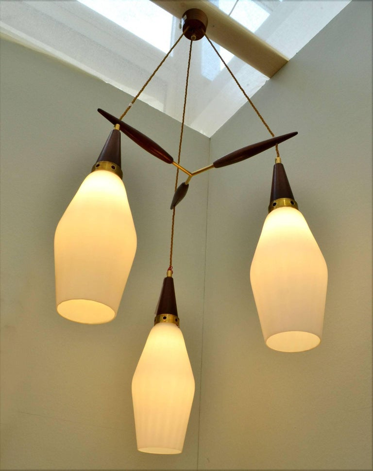 The three pendants are in dark teak wood, brass and opaline glass shades spaced by a teak and brass suspension and connected to a teak ceiling rose. Dimensions of each pendant: Height 40 cm, diameter 19 cm. Each shade assembly can be adjusted in