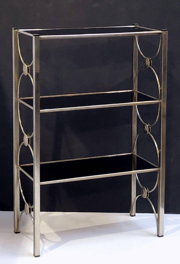 A fine English open étagère or shelves, featuring a brushed metal frame and three removable rectangular shelves of black glass. Glass shelves can be reversed for a different look.  Dimensions: H 36 inches x W 23 1/2 inches x D 12 inches
