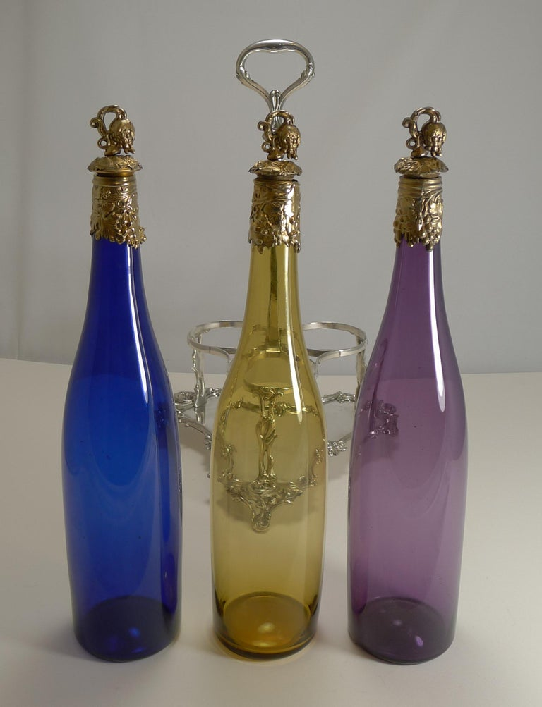 A magnificent set of three late Victorian colored glass decanters, all with polished pontil marks on the underside showing that they were individually hand blown; one in golden yellow, one in Amethyst and one in cobalt blue.  Each is topped with a