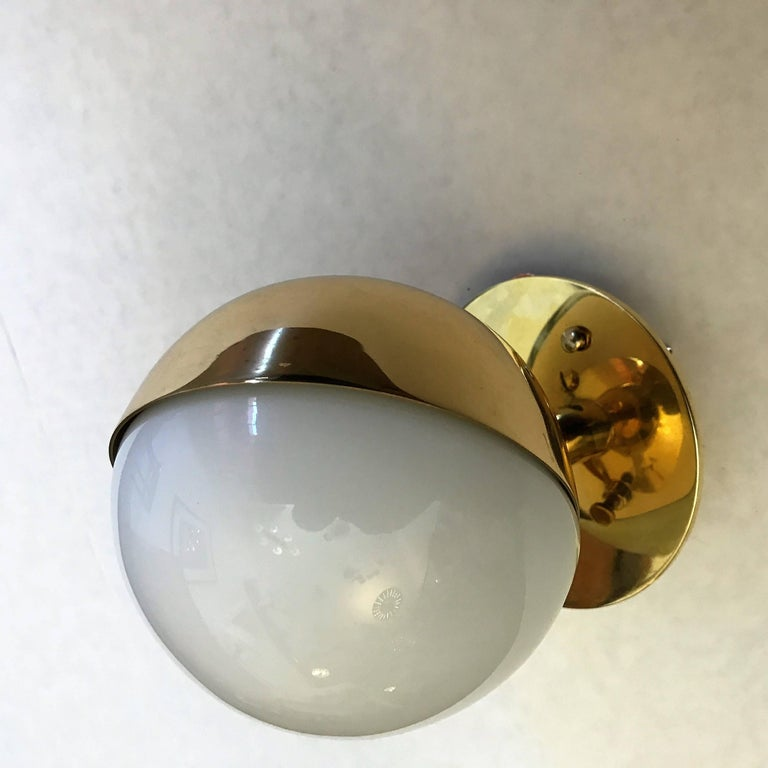An original set of three Bauhaus style 1920s polished brass and white opaline glass wall lights designed by Vilhelm Lauritzen for Poulsen. Rewired. The lights can tilt and be set in the optimal direction with its set screw.