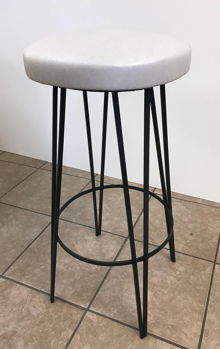 Three vintage wrought iron stools with off-white leatherette seats.