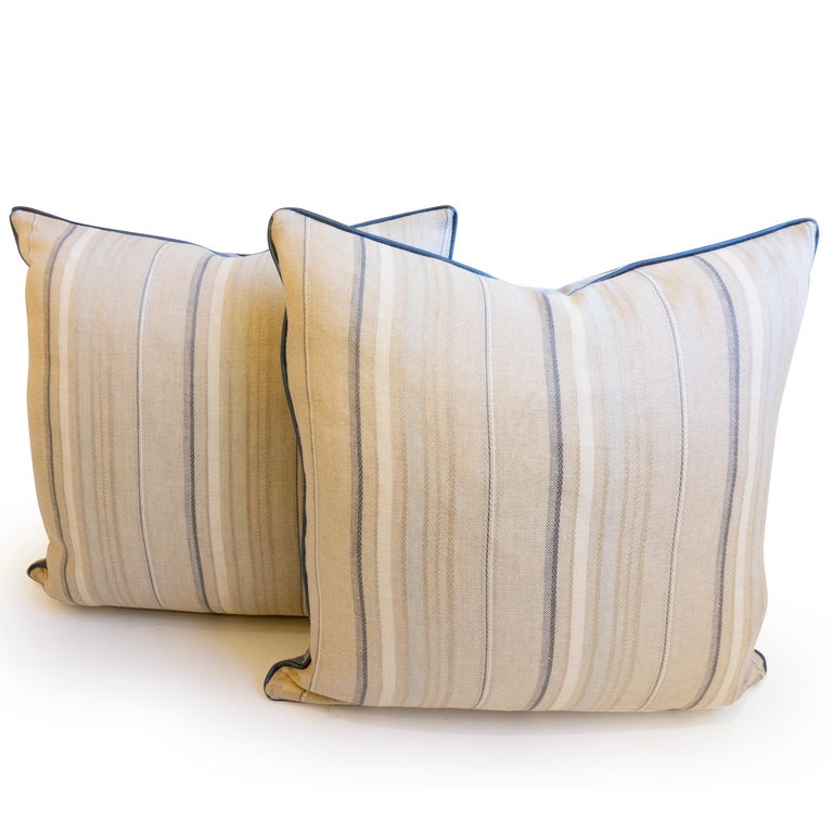 This pair of throw pillows were hand sewn at our studio in Norwalk, Connecticut. The pillows feature a linen pinstripe pattern on the front and a soft blue velvet on the back. Each pillow is trimmed with a blue vinyl piping that has a hint of shine