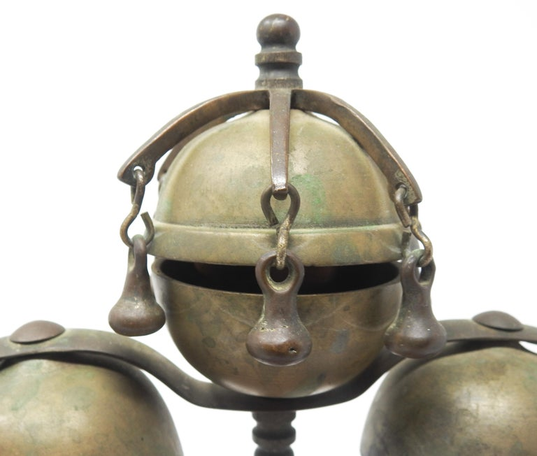 Offering these gorgeous bronze and brass meditation bells on wood stand from the late 19th Century. Starting on a handcrafted wood base that is very geometric. The curved arms holding the bells rise gracefully and meet in the middle. There are two