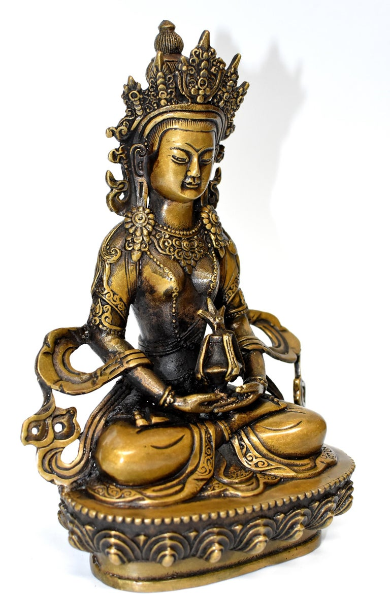 The beautiful bronze sculpture is of The Tibetan Amitayus, the Bodhissatva/Buddha of infinite life. Adorned with necklaces, crown and sashes decorated with rosettes, pearls and medallions, Buddha is seated on a lotus throne, holding Kalasa which is