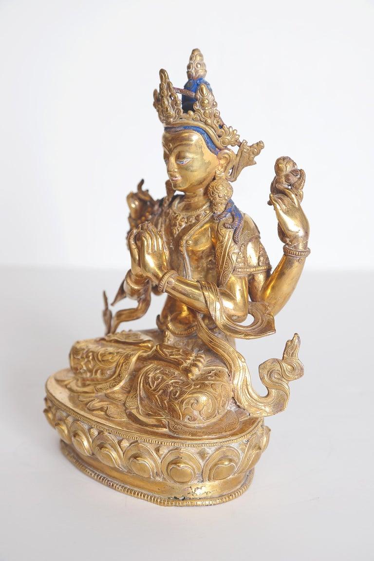 Tibetian Buddhist Deity Chenrezig (Four-Armed Avalokiteshvara), gilt metal / brass with blue hair, red inside of crown  Measures: 10.5
