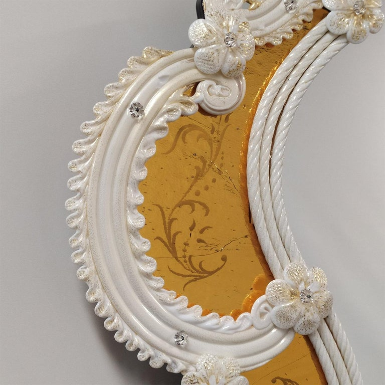 A gorgeous design of unparalleled elegance, this wall mirror sublimely reproduces the refined figure of an ancient Venetian style mirror, interpreted in a modern key with a new and brilliant choice of colors. Engraved by hand on an amber mirror, it
