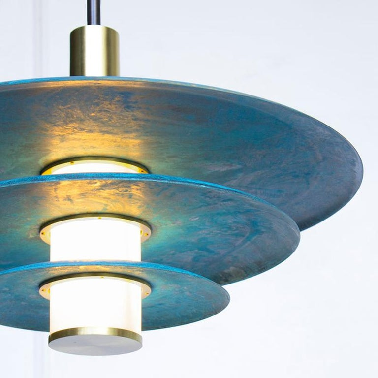 The tiered Arthur pendant embraces Trella's Prussian blue patina in grand fashion. An internally lit white glass cylinder illuminates the depth of the hand applied patina while simultaneously providing a soft accent light. The three tiered Arthur
