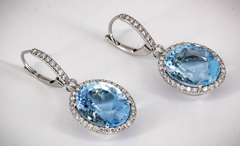 Elegant aquamarine, diamond and platinum earrings by Tiffany & Co. They feature a large aquamarine as the central stone, approx. 11-12 carats total weight, surrounded by high grade round brilliant cut diamonds over a platinum setting.  Hallmarks: