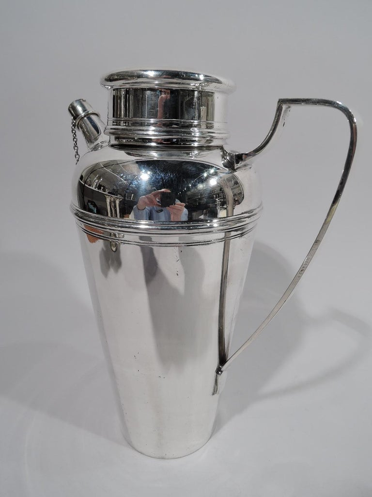 Art Deco sterling silver cocktail shaker. Made by Tiffany & Co. in New York, circa 1925. Straight and tapering bowl with curved shoulder, high scrolled bracket handle, short neck with overhanging flat-topped cover, and stubby, tapering spout with