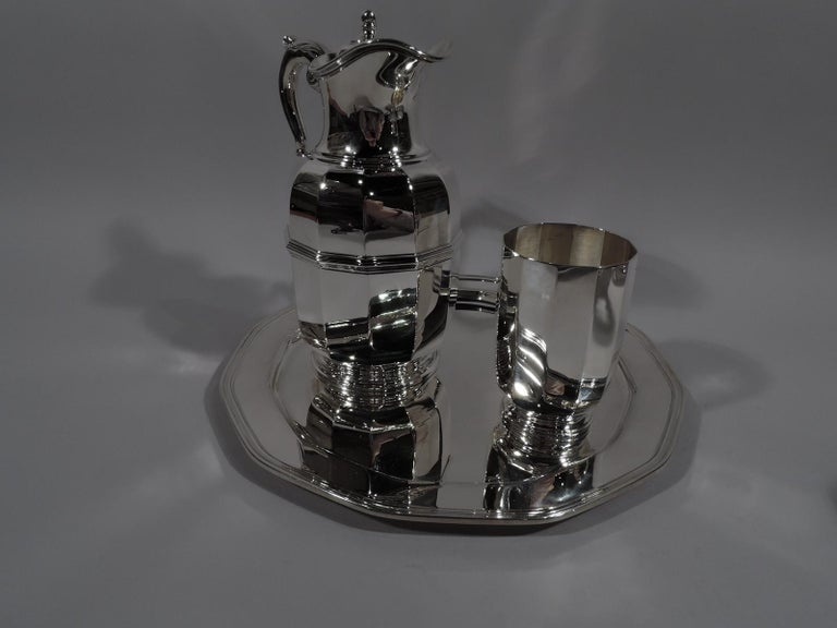 Art Deco sterling silver drinks set for one. Made by Tiffany & Co. in New York, circa 1930. This set comprises carafe, cup, and tray in the faceted geometric style.  Carafe has curved sides with girdle, leaf-capped s-scroll handle, stepped foot.